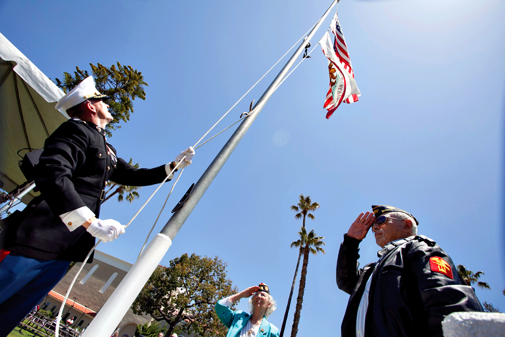 World War II veterans Oscar Vizcarra (right) and Anna Brown (center) help Lt. Col. Douglas Woodhams, a Marine and Santa Monica Police officer, raise the flag during the 74th annual Memorial Day Observance at the Woodlawn Cemetery earlier this year. (Brandon Wise brandonw@smdp.com)