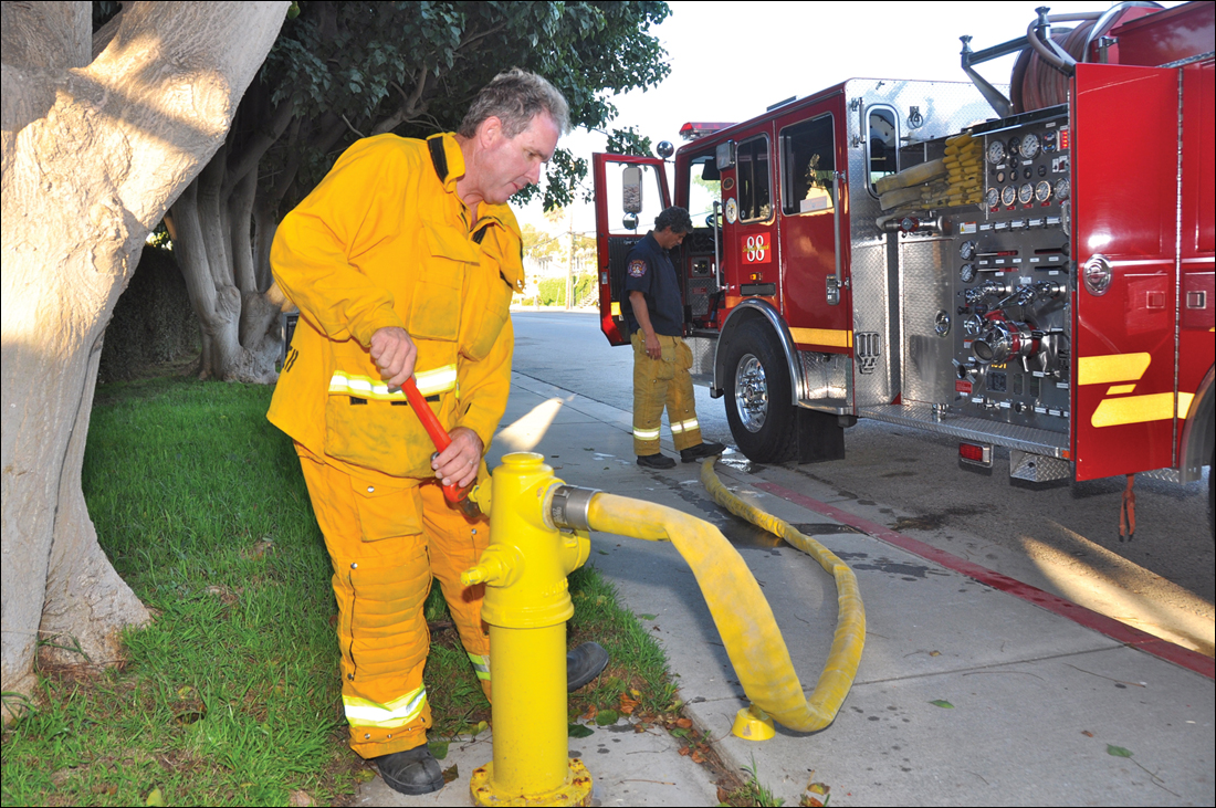 Engineer John Steindlberger hooks up a hose to a fire hydrant after a long day of emergency calls recently. (Julie Ellerton)