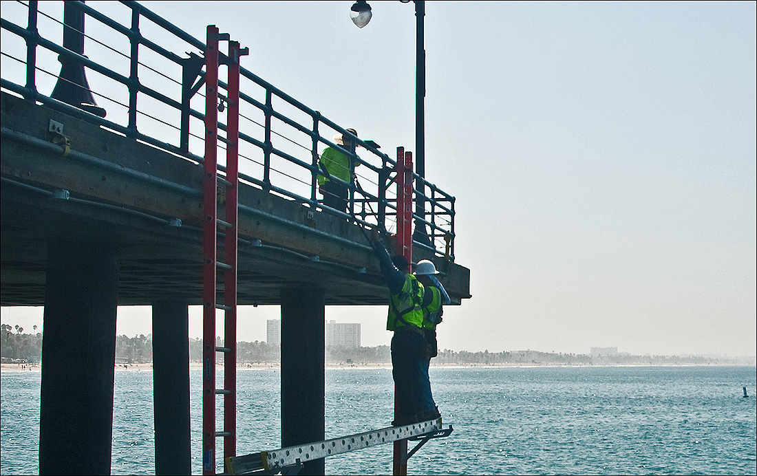 LET THERE BE LIGHT: Electricians replace florescent lights and fixtures with LED versions at the Santa Monica Pier on Monday. (Fabian Lewkowicz FabianLewkowicz.com)