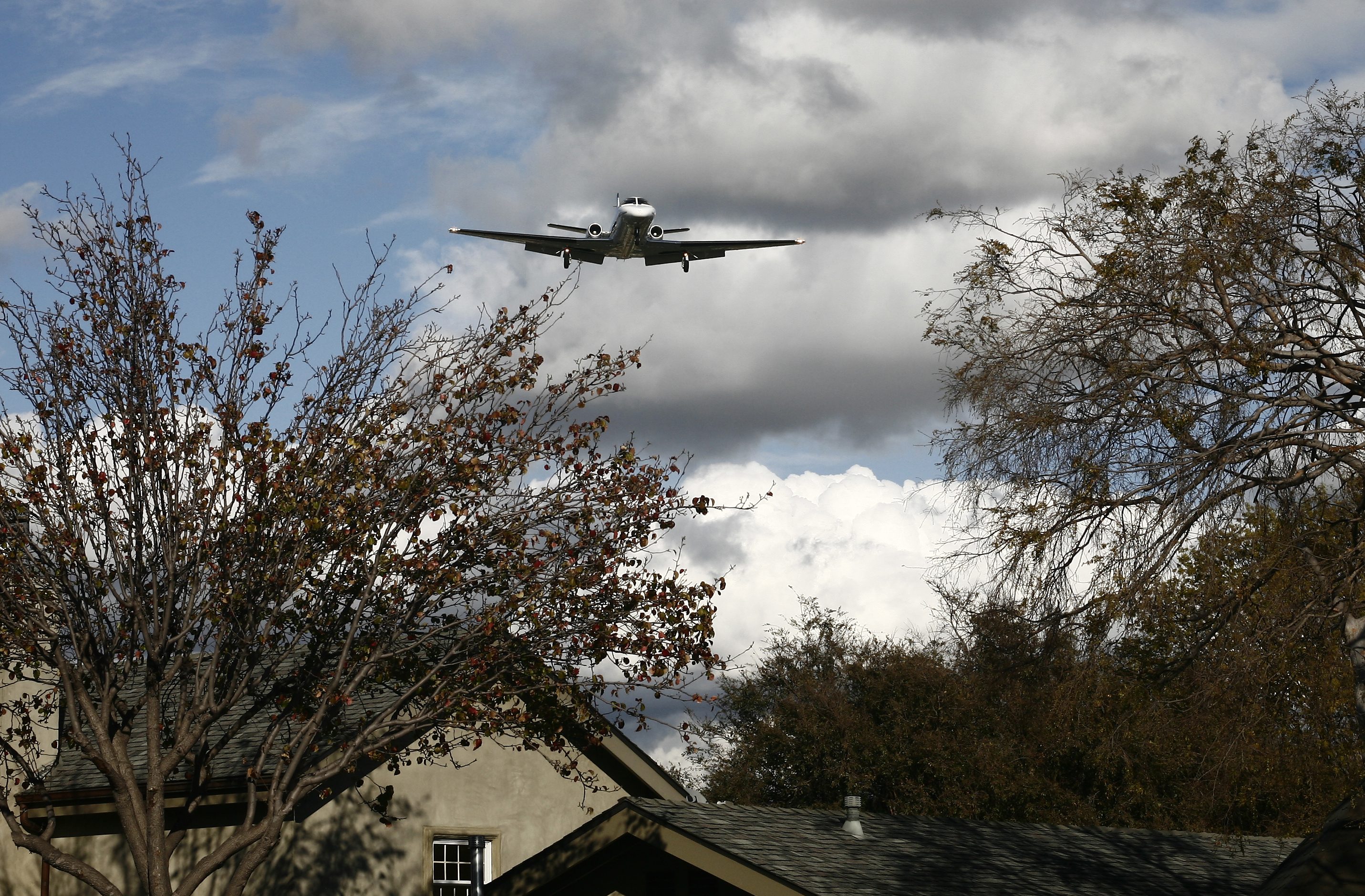 A jet flies over a home off of Bundy Drive as it makes its way to Santa Monica Airport. A majority of City Council candidates said they would be in favor of closing it or curtailing operations. (File photo)