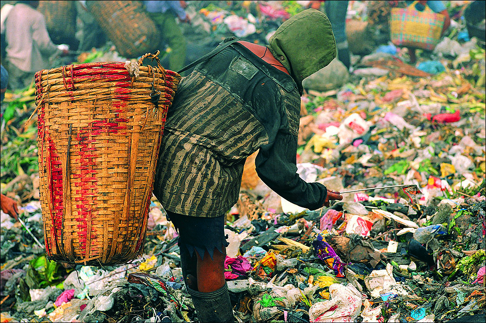 BIG NUMBERS: The number of people on the planet has doubled from 3.5 billion to seven billion in just a half century. The most obvious issue with so many of us here is our profligate consumption of dwindling natural resources and the waste and pollution generated in the process. Pictured: A person surviving on waste in the Philippines. (Photo courtesy StockByte/Thinkstock)