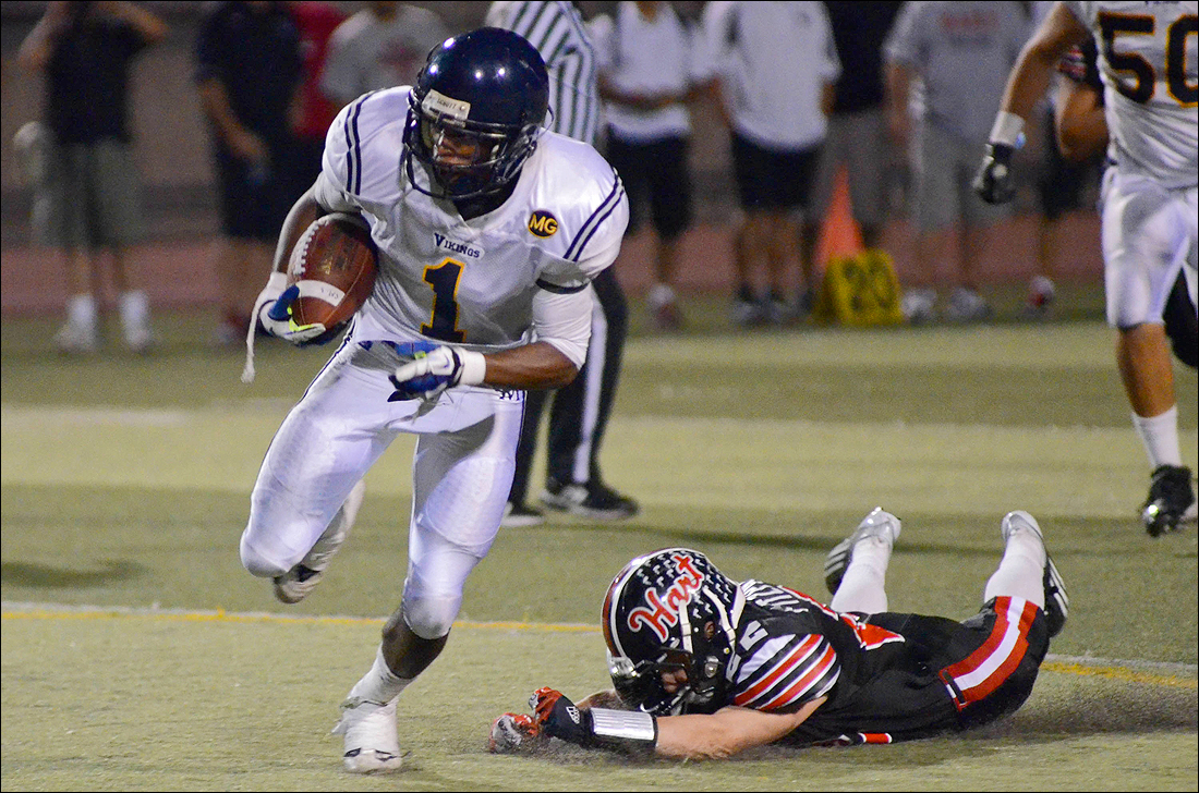 HEADED DOWNFIELD: Santa Monica wide receiver Sebastian LaRue runs past a Hart defender last Friday during a loss. (Photo by Paul Alvarez Jr.)