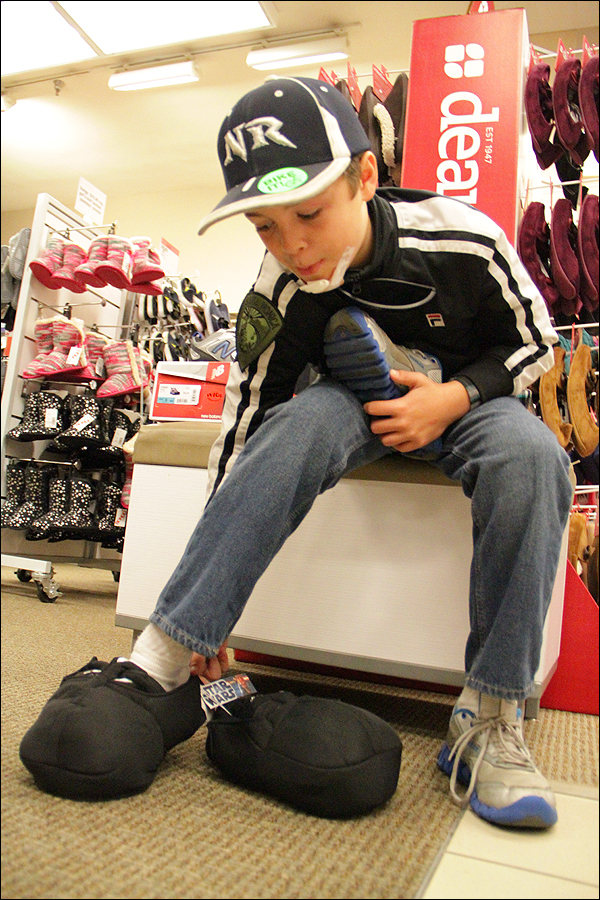 COOL KICKS: Alex Petrakos tries on a pair of slippers during a shopping trip to Sears. (Photo by Daniel Archuleta)