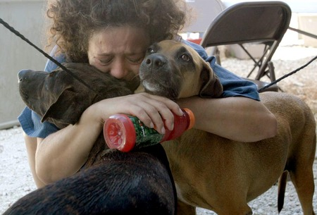 Zona Marchand hugs her dogs Game (left) and Kira before leaving them at the Noah's Wish emergency animal shelter in Slidell, La. following hurricane Katrina. (Photo courtesy Google Images.)