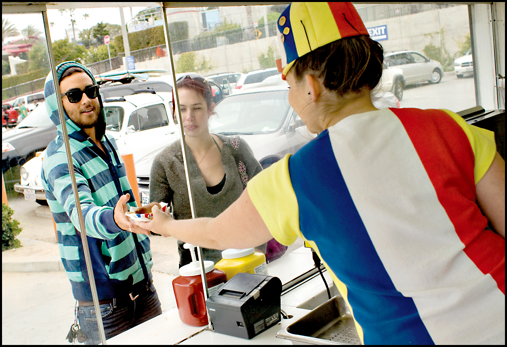 Employee Jenny West serves a corndog to locals Trevor Holst and Madison Spencer at the Hot Dog on a Stick on Ocean Front Walk . (Photo by Brandon Wise)