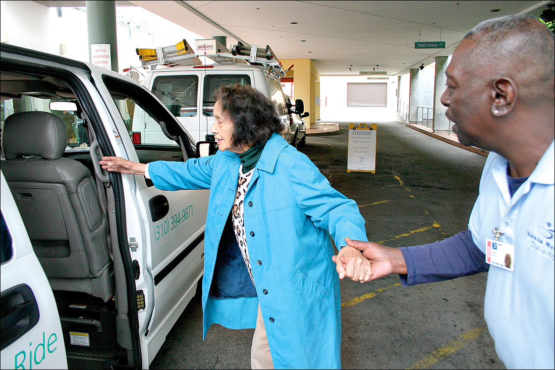 helping hand: Dial-a-Ride driver LB Brown (right) helps senior Aurora Vasquez board his bus outside of WISE & Healthy Aging.  (File photo)