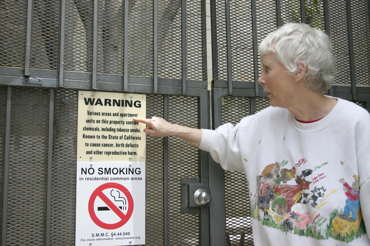 Bette Shapiro points out a 'no smoking' sign at her apartment complex on Fifth Street earlier this year before the City Council voted to ban smoking in apartments and condos for all those moving in after Nov. 22. (File photo)