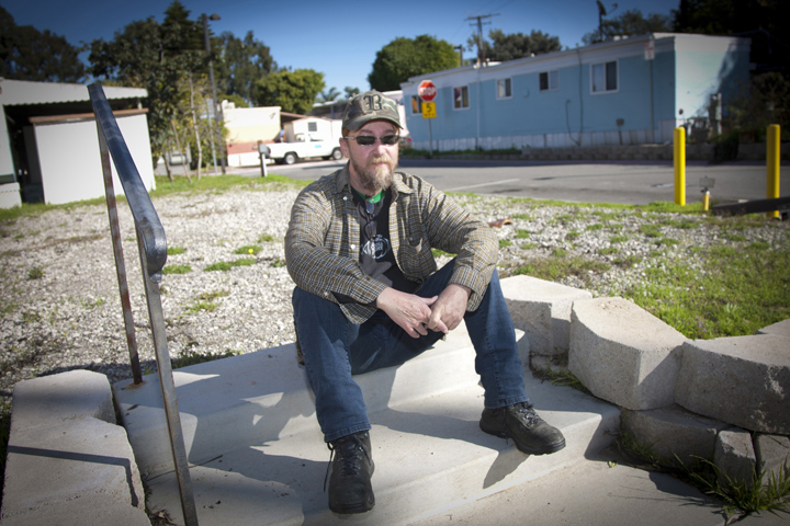 Cris McLeod sits in front of a vacant lot at Mountain View Mobile Home Park on Friday afternoon. He is one of a handful of residents who have filed a $121 million claim against City Hall for allegedly failing to maintain the park and treat tenants fairly. (Brandon Wise brandonw@smdp.com)