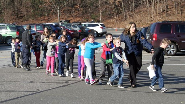 Students at Sandy Hook Elementary School in Connecticut are evacuated Friday following a deadly shooting in which 20 children were killed by a lone gunman. (Photo courtesy Getty Images)
