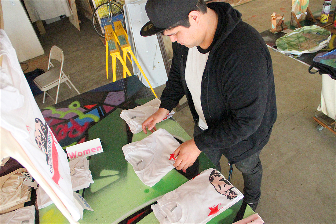 Artist Bobby Rodriguez on Wednesday folds one of the shirts he created for Streetcraft L.A., a pop-up shop that has opened its doors on Main Street. (Photo by Daniel Archuleta)
