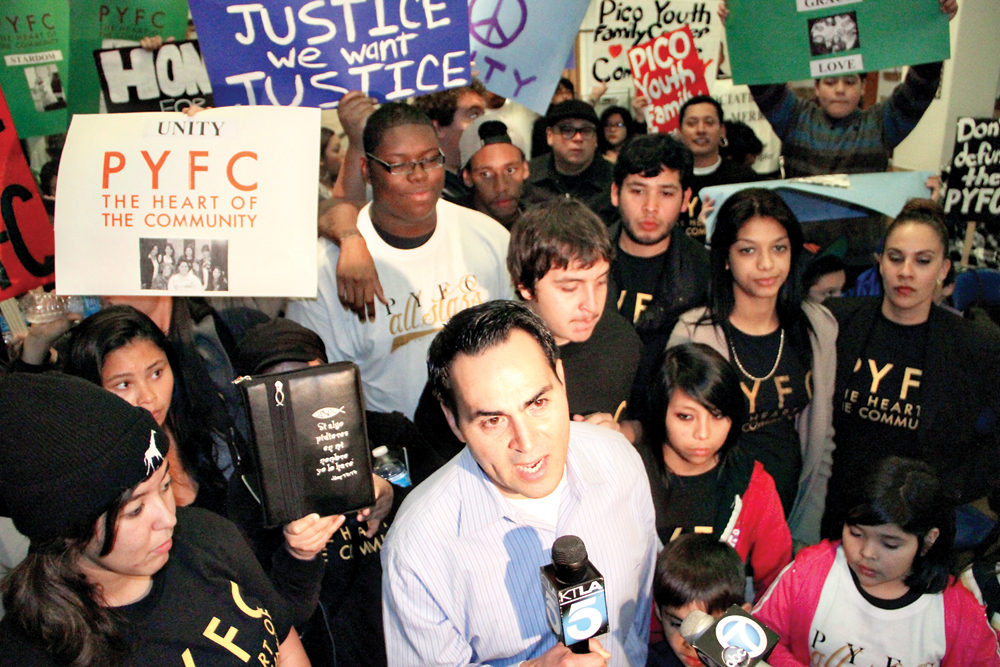 Pico Youth & Family Center founder Oscar de la Torre speaks to newscrews Tuesday amid a group of protestors asking the City Council to continue funding for the embattled center. (Daniel Archuleta daniela@smdp.com)