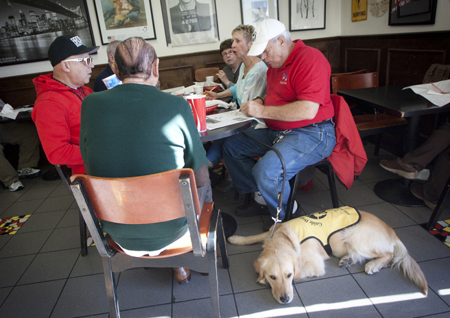 Friends enjoy crossword puzzles and bagels with Glyn Judson (right) and his golden retriever guide dog Fred at New York Bagel and Deli on Wilshire Boulevard on Monday morning. (Brandon Wise brandonw@smdp.com)