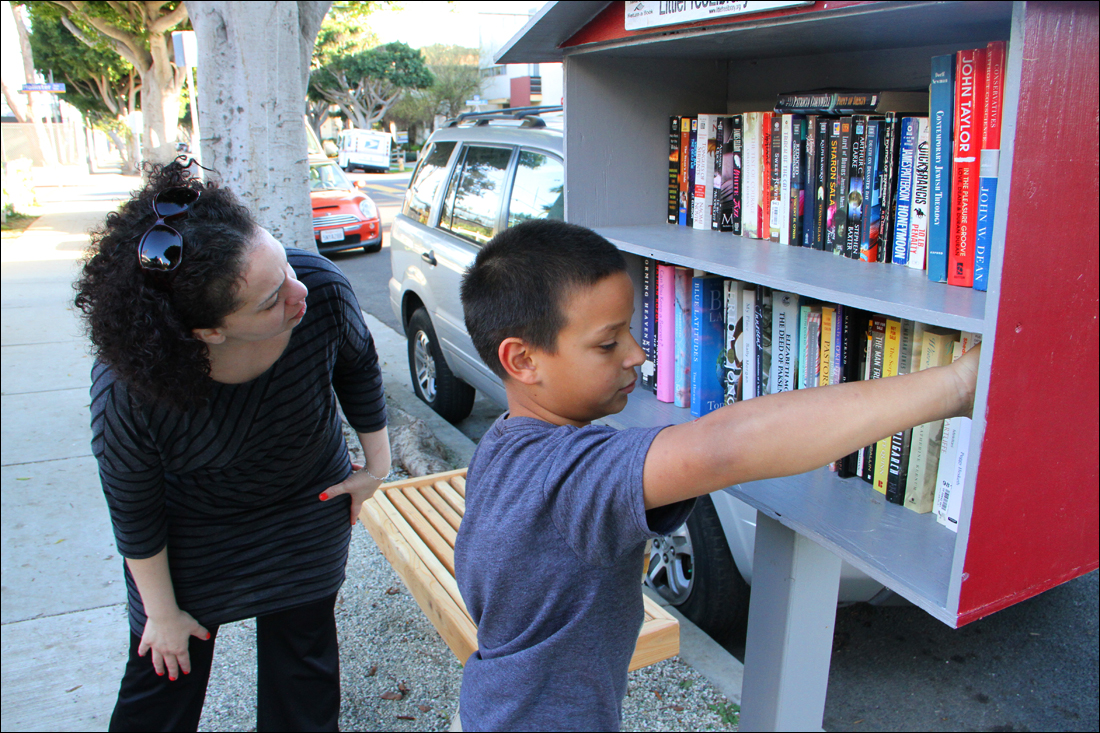 CHECKING IT OUT: Simon Johnson, 9, stocks books in his mother's Little Free Library on Monday as Santa Monica arts commissioner Tanya Merriman browses the selection. The library is part of an international effort to spread the written word. (Photo by Daniel Archuleta)