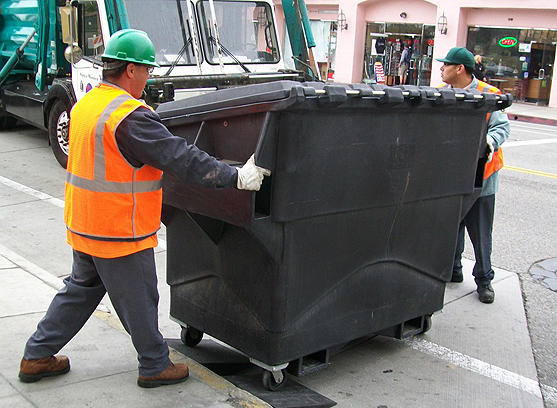 Garbage men use rubber ramps to move more easily a dumpster on Montana Avenue. The ramps were made from recycled tires. (Photo courtesy city of Santa Monica)