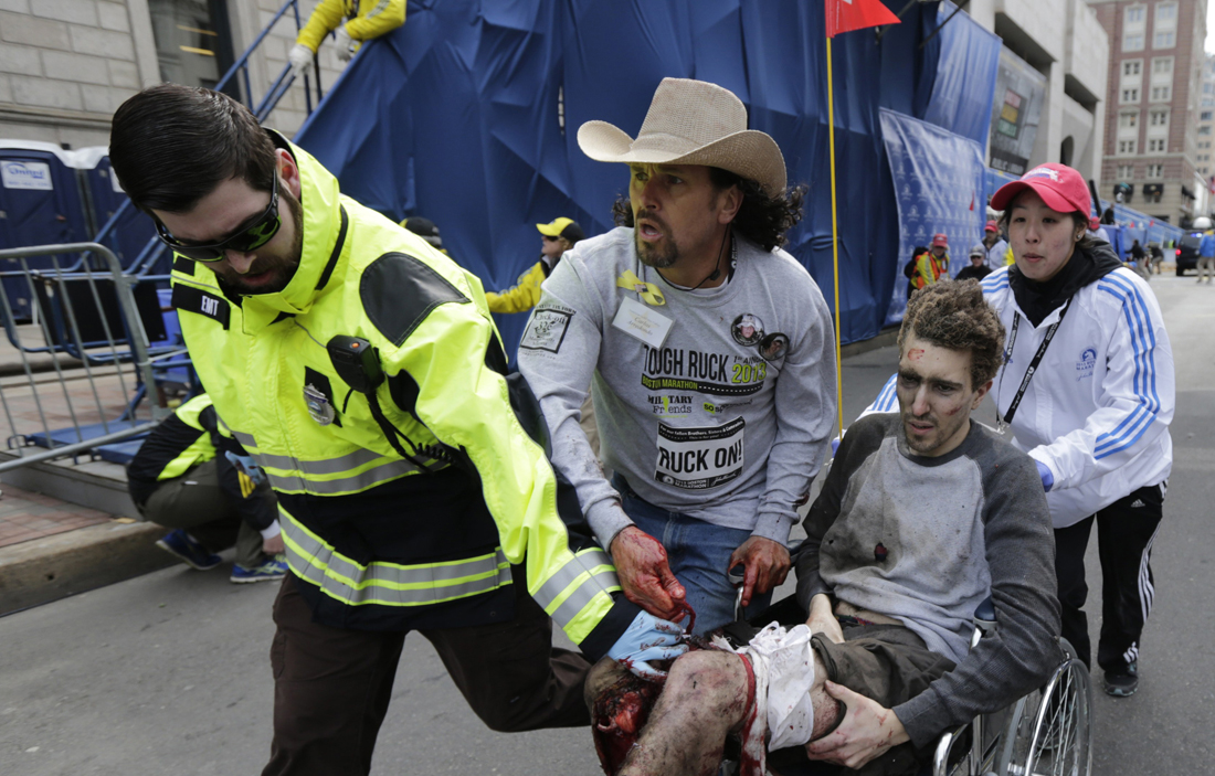 TRAGIC: Medical responders run an injured man past the finish line of the 2013 Boston Marathon following an explosion in Boston on Monday. (Associated Press)
