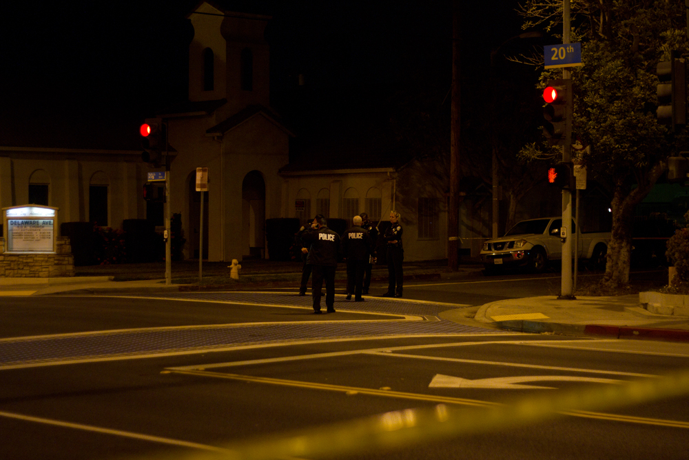 Police gather Tuesday night at the corner of Delaware Avenue and 20th Street, the site of a possible gang-related shooting in which a woman was shot in the shoulder. (Doug Olmedo editor@smdp.com)