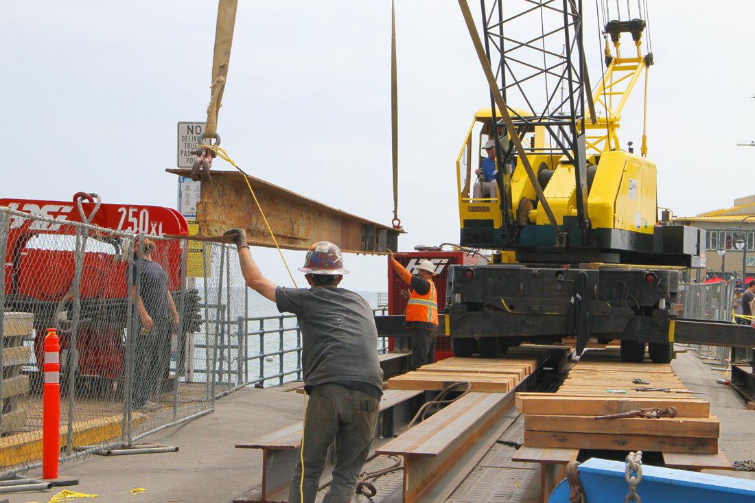 A work crew hoists a massive I-beam onto the deck of the Santa Monica Pier. The work is part of a the pier's Renewal Project. Much of the project will be focused on replacing most of the deck from the waterline to the western end of the historic landmark.