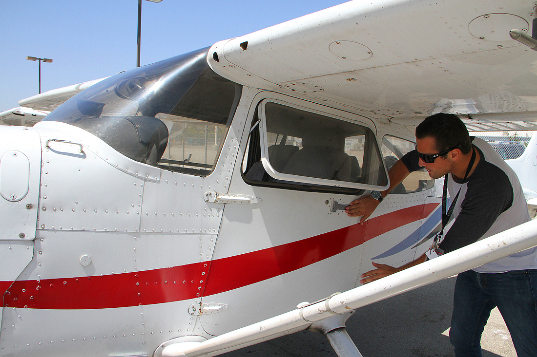 PREFLIGHT: Justice Aviation instructor Jordan LaMotte inspects one of the company's planes. (Photo by Daniel Archuleta)