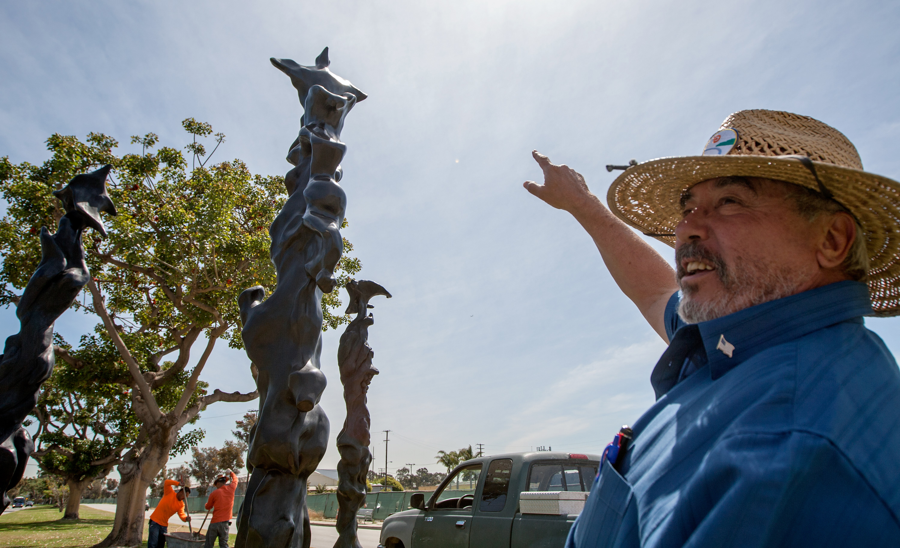 Public Works inspector Ramon Gutierrez oversees the final stages of the installation of Herb Alpert's 'Black Totems' sculptures on Friday at the corner of Olympic Boulevard and 26th Street. Grammy-winning musician and artist Alpert drew his inspiration for the pieces from totem poles from indigenous tribes in the Pacific Northwest. (Michael Yanow editor@smdp.com)