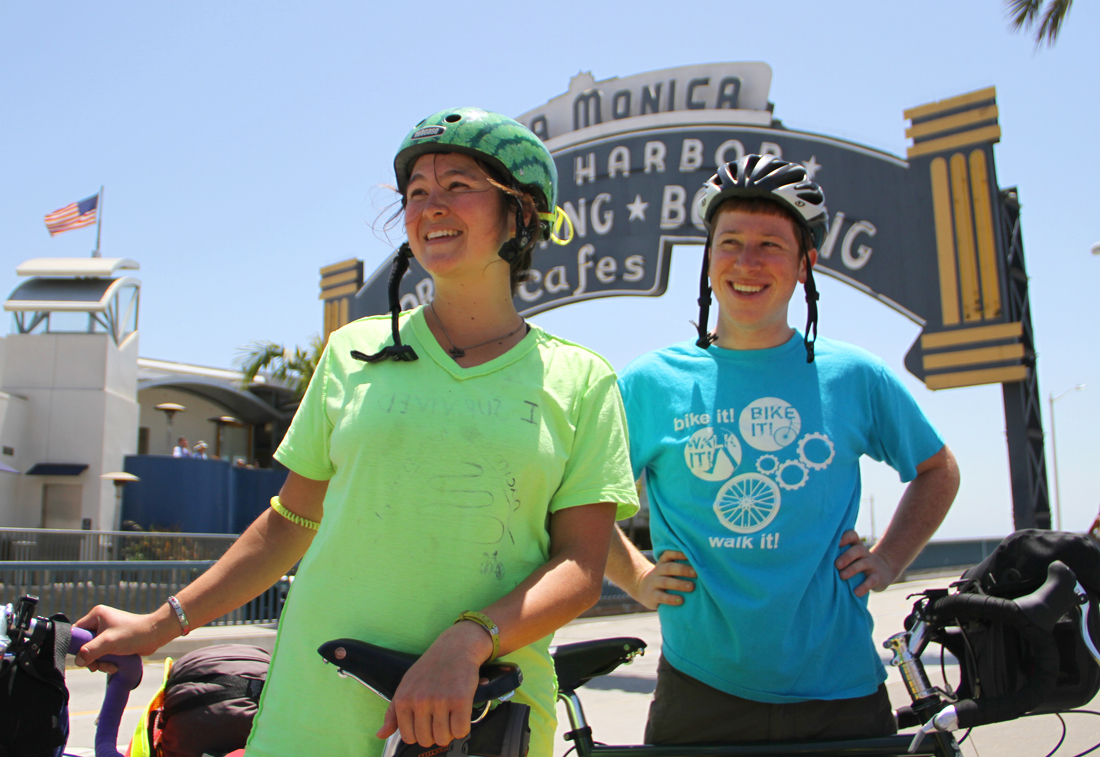 Rachel Horn and Owen Gorman pose under the Santa Monica Pier sign in the days leading up to their cross-country journey. (Photo by Daniel Archuleta)