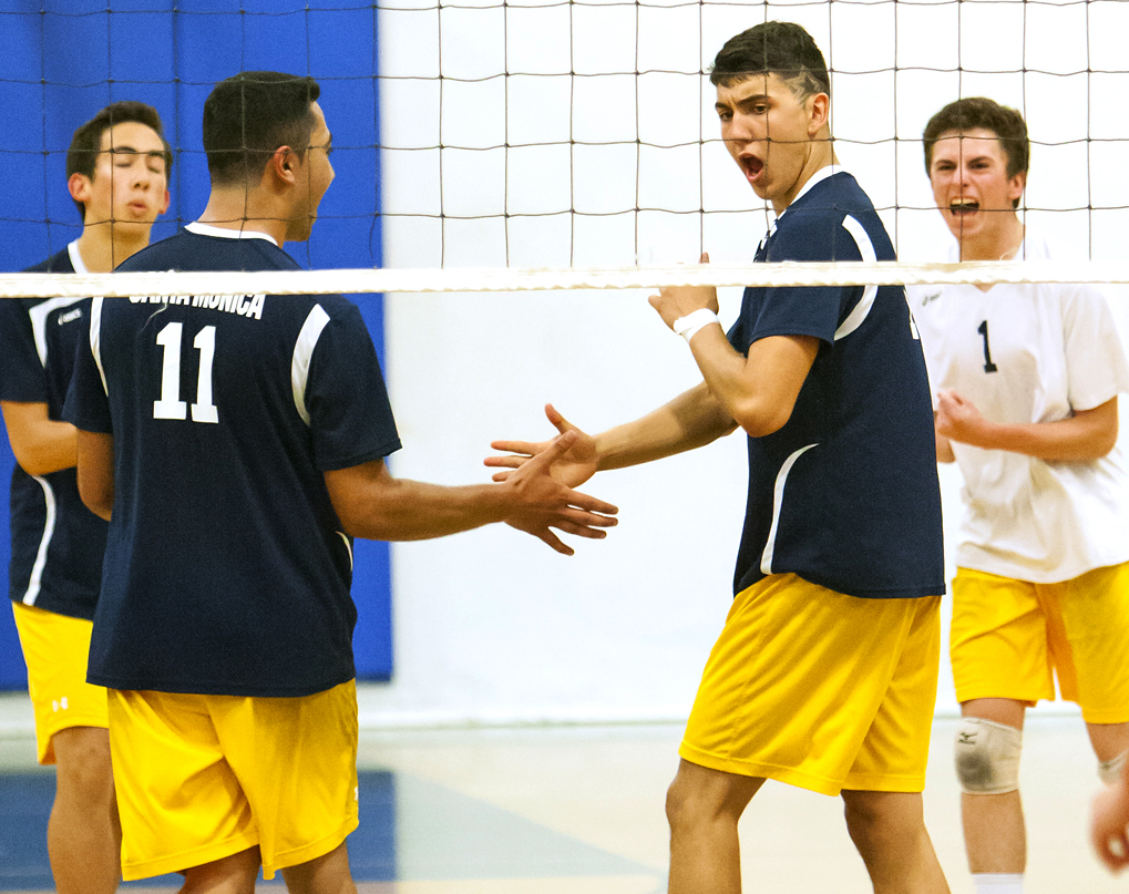 YUP! Isan Contrera (right) of Santa Monica celebrates after scoring a point against the defense of Whittier Christian in the first round of the CIF-Southern Section Division 3 boys' volleyball playoffs at Santa Monica High School on Tuesday. Samohi won in straight sets, 25-18, 25-15, 25-19, to advance to the next round. (Photo by Michael Yanow)