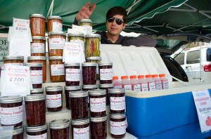 Kris Gean shows off the products he sells at the Downtown Farmers' Market. (Photo by Paul Alvarez Jr.)