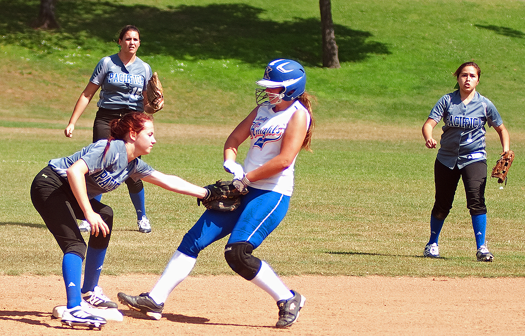SHE'S OUT: Pacifica Christian's Spencer Dolan (left) tags out Academy for Academic Excellence's Alyssa Fredrick while teammates watch on Tuesday at Clover Park. Pacifica Christian went on to lose the second round playoff game, 12-0. (Photo by Morgan Genser)