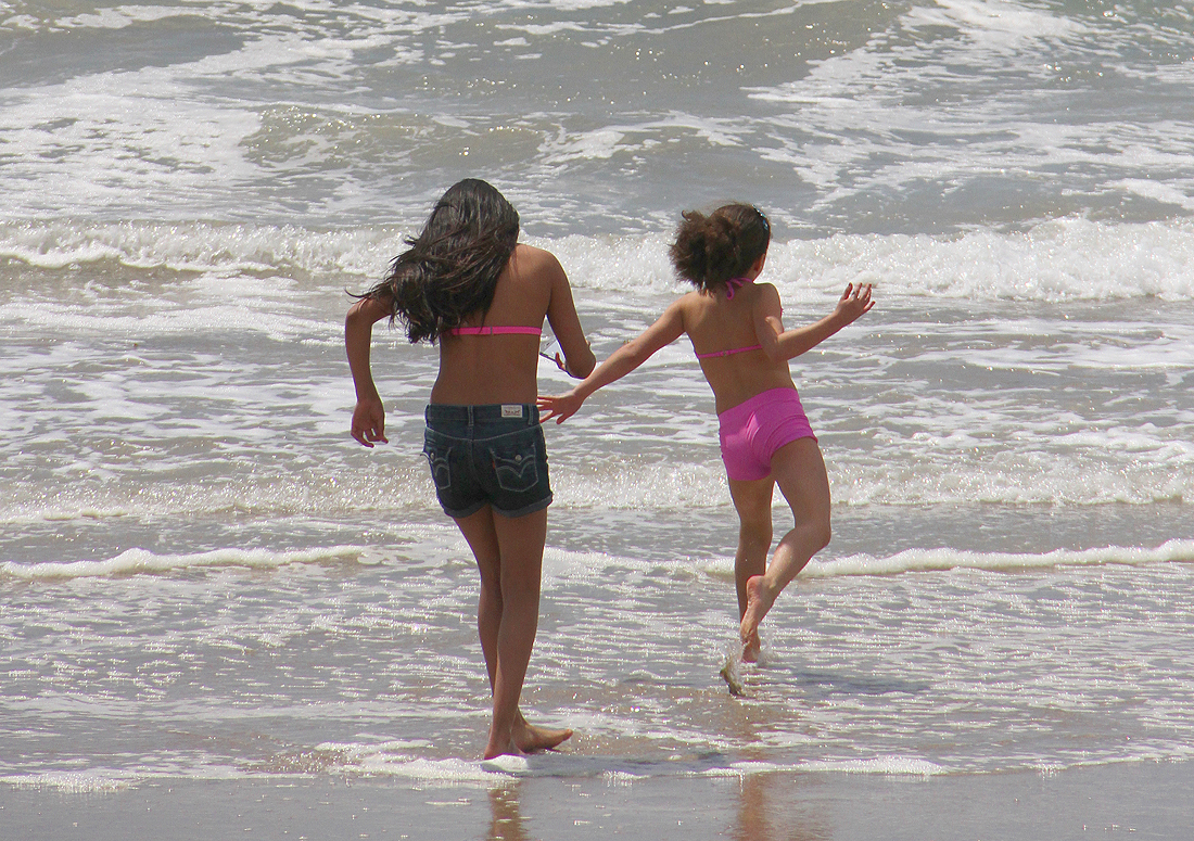 A pair of young girls play in the surf at Santa Monica State Beach earlier this year. (Photo by Daniel Archuleta)
