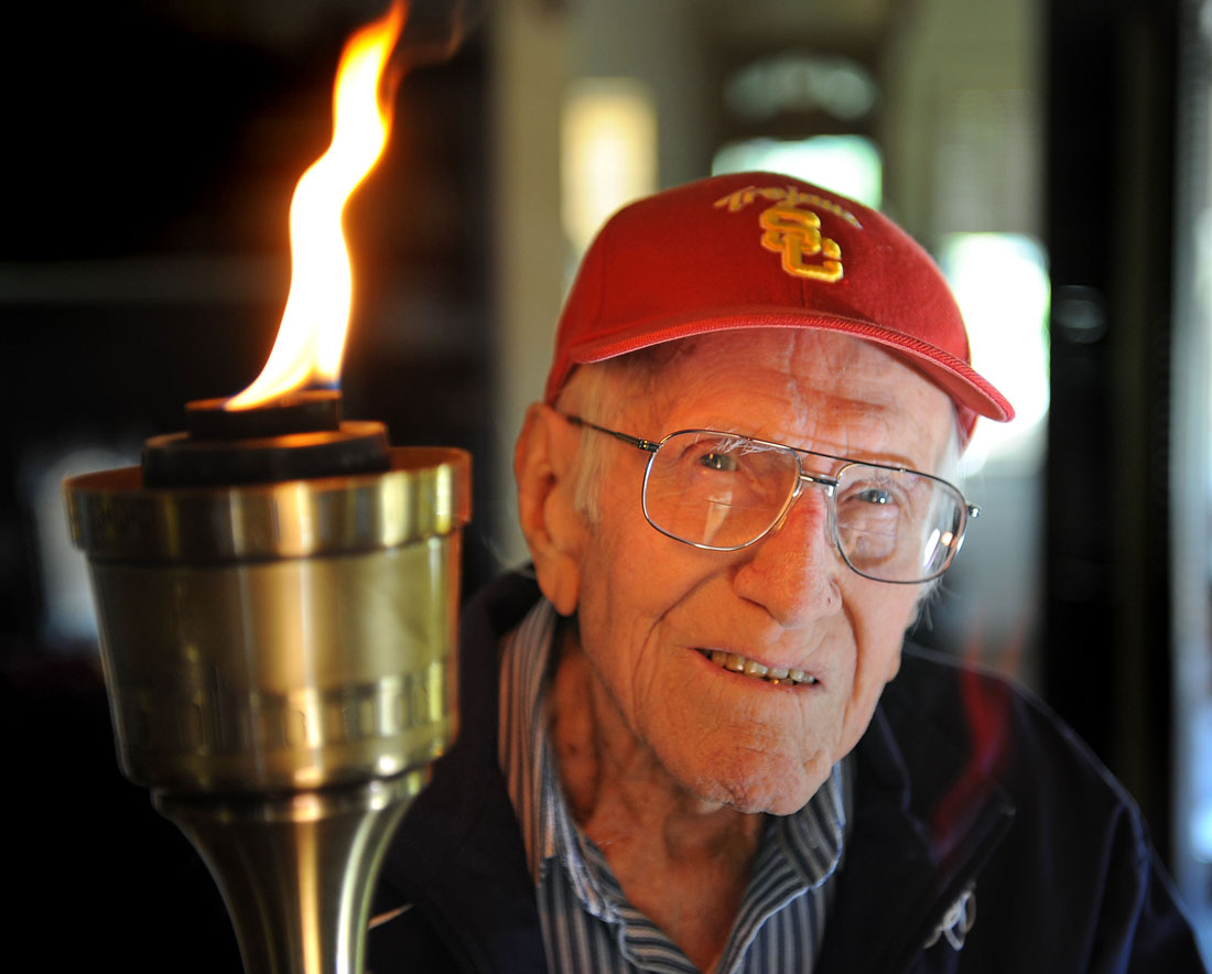 Louis Zamperini, 96, at his Hollywood home. The flame still burns in him as he holds the olympic torch he carried at the 1984 Olympic Games. (Photo by Brad Graverson)