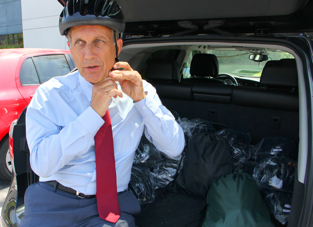 Local attorney Peter Steinberg puts on one of the helmets he is handing out for free to bike riders who don't wear them. (Photo by Daniel Archuleta)