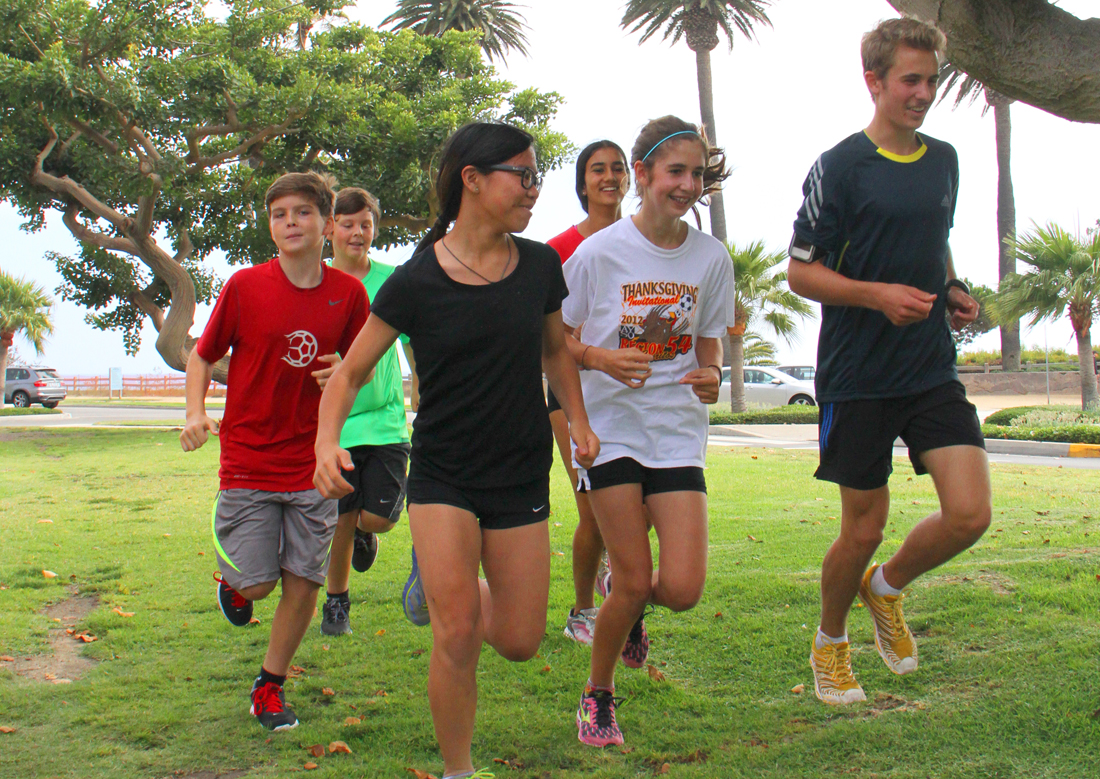 Justin Sardo (right) leads the Santa Monica Youth Running Club down the median on San Vicente Boulevard on Wednesday. (Daniel Archuleta daniela@smdp.com)