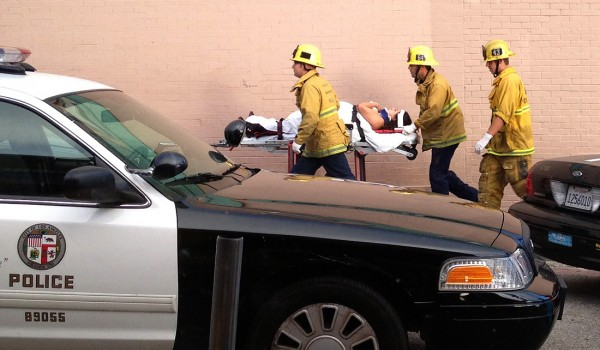 AFTERMATH: Fire personnel whisk a victim away from the scene of a deadly car crash on the Venice boardwalk last Saturday. (Photo courtesy Byron Kennerly)