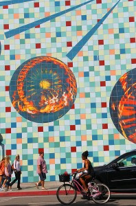 BUSTLING: Downtown visitors pass by a massive mural on Second Street on Thursday. (Daniel Archuleta daniela@smdp.com)
