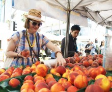 KEEN ON PEACHES: Coralie Winn, one of the GOOD Exchange fellows, picks out some peaches from one of the stands at the Downtown Farmers' Market on Wednesday morning. The fellows were at the market to learn about its storied history. (Paul Alvarez Jr. editor@smdp.com)