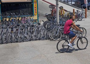 WHEELS FOR DAYS: A man rides his bike past a popular bicycle rental shop near the foot of the Santa Monica Pier. (File photo)