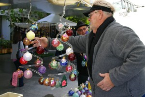 CHECKING OUT THE MERCHANDISE: Ed Broadfield adjusts his display of hand-blown ornaments during the Contemporary Crafts Market at the Santa Monica Civic Auditorium last year. (File photo)