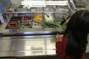 In this photo from last year a student at Will Rogers Elementary School grabs some celery sticks from the salad bar, which is stocked mostly with food purchased at one of the Santa Monica Farmers' Markets.