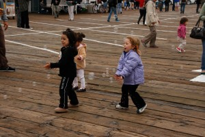 Children at the Santa Monica Pier enjoy playing with floating bubbles. (File photo)