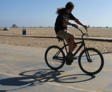 A man rides his bike along the beach bike path on Tuesday.