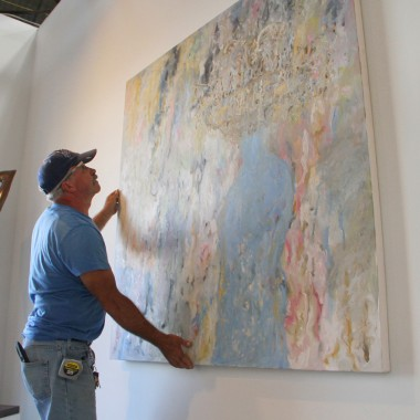 Jose Perez hangs a work by Yossi Govrin at the Santa Monica Art Studios on Wednesday. (Daniel Archuleta daniela@smdp.com)