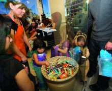 Trick-or-treaters grab candy at a nail salon on Montana Avenue. (File photo)