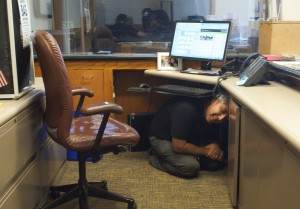 SAFETY FIRST: City Hall receptionist Jeff Snyder covers under his desk during The Great California ShakeOut drill on Thursday morning. (Paul Alvarez Jr. editor@smdp.com)