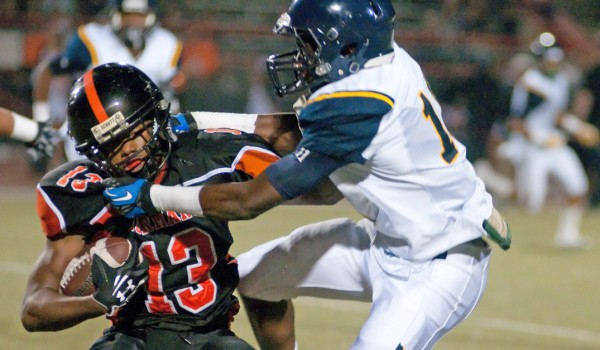 Samohi's Ahmad Clayton (right) tackles Beverly Hills' Damiyon Brown on Friday on the road. (Morgan Genser editor@smdp.com)
