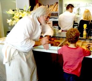 Chef Alain Giraud helps a young customer at the pastry counter of his Palisades restaurant Maison Giraud. ( Photo courtesy John Blanchette)