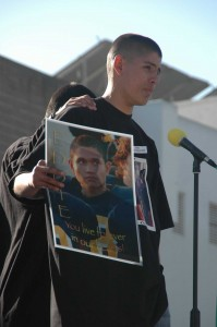 A friend of Eduardo 'Eddie' Lopez, 15, holds up a photo of the young man during a memorial service at Santa Monica High School in 2006. Lopez was shot and killed while walking with friends along Pico Boulevard. (File photo)