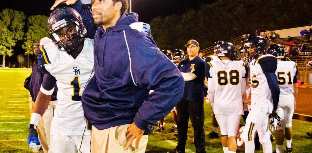 STANDING UNITED: Samohi senior Kwame Duggins hugs head coach Travis Clark late in the fourth quarter on Friday night at Lompoc High School during what would be a 42-10 playoff loss. (Paul Alvarez Jr. editor@smdp.com)