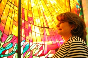 SO COLORFUL: Woodlawn Cemetery boss Cindy Tomlinson stands in front of a stained glass window at the facility. (Daniel Archuleta daniela@smdp.com)