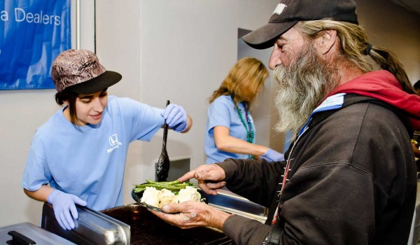 PITCHING IN: Leah Dietrich (left) volunteered during an event to feed the homeless hosted by Honda Motors at the Civic Auditorium on Friday. (Paul Alvarez Jr. editor@smdp.com)