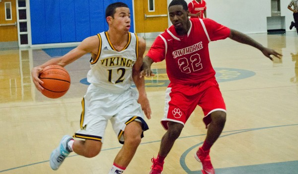 DRIVING: Santa Monica High School's Chris Johnson dribbles past a Hawthorne defender Wednesday night at Samohi. The Vikings went on to win the Ocean League game, 61-45. (Paul Alvarez Jr. editor@smdp.com)