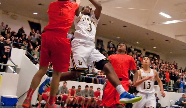 MAKING A GO OF IT: Santa Monica High School's Mikhail Brown attempts a shot against Beverly Hills on Friday at home. Beverly Hills walked away with the win, 58-45, and seized control of first place in the Ocean League in the process.  (Morgan Genser editor@smdp.com)
